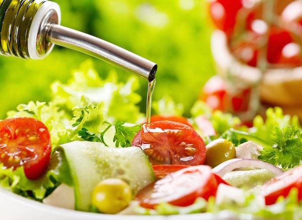Friss zöldségekből készült salátára öntenek olívaolajat.