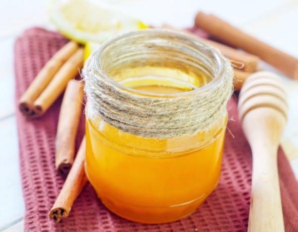 Spárgával körbetekert üvegben méz, mellette fahéjrudak, mézkanál és citrom.