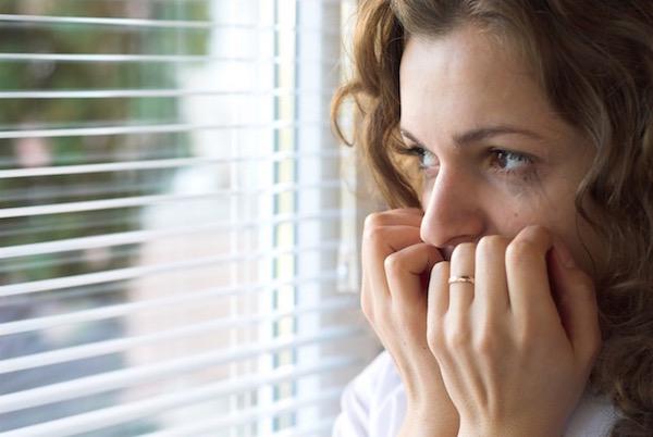 Fiatal, szorongó lány néz ki körmét rágva az ablakon.