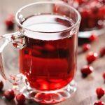 Vörös áfonyából készült gyümölcslé üvegpohárban, mellette áfonyaszemek.