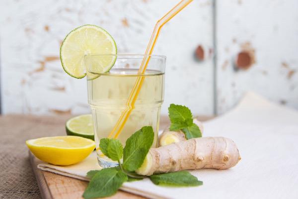 Gyömbérből készült frissítő ital szívószállal, mellette félbevágott lime és citrom.