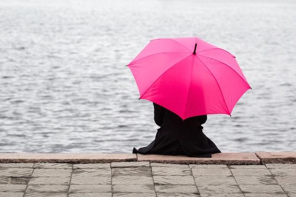 Egyedül ül az esőben a folyó rakpartján egy fekete kabátos nő, kezében pink esernyő.