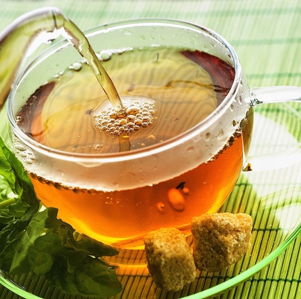 Gyógynövényből készült tea nőknek üvegcsészében barna cukorral.