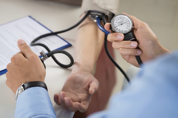 Kék inges orvos méri vérnyomását páciensének.