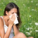 Zöld mező közepén orrát fújja egy barna hajú lány, aki valószínűleg allergiás.