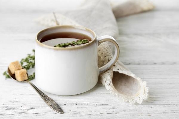 Kakukkfűtea fehér bögrében, a tetején friss kakukkfűszálacskával, mellette kiskanálban két szem barna kockacukor, a csésze mellett horgolt szalvéta.