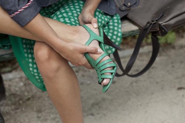 Zöld magassarkú szandálba bújtatott lábát masszírozza egy pöttyös szoknyás nő.