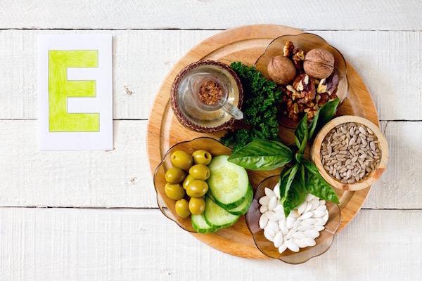 E-vitamint tartalmazó élelmiszerek összegyűjtve egy fából készült tálcán, mellette egy nagy sárga E betű.