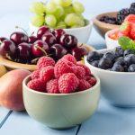 Nyári gyümölcsök kis tálkákba rakva: málna, sárgabarack, eper, áfonya, szeder, szőlő és megy.