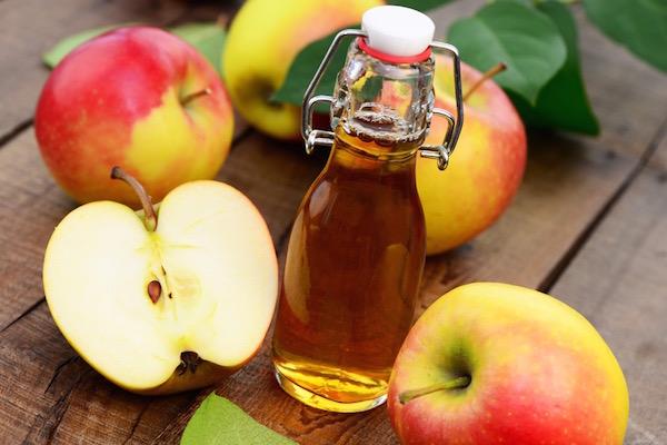Egész és félbevágott almák, köztük egy kicsi csatos üvegben almaecet.
