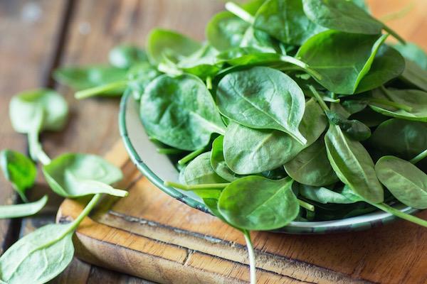 Friss spenótlevelek egy zöld szélű kis tálkában egy faasztalon.