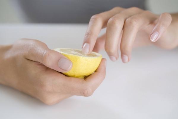 Szépen manikűrözött kezével egy félbevágott citromot tart egy hölgy, így fehéríti mutatóujja körmét.