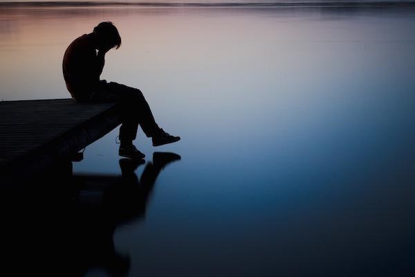 Fiatal férfi magába borulva ül egy pad szélén, arcát kezébe temeti.