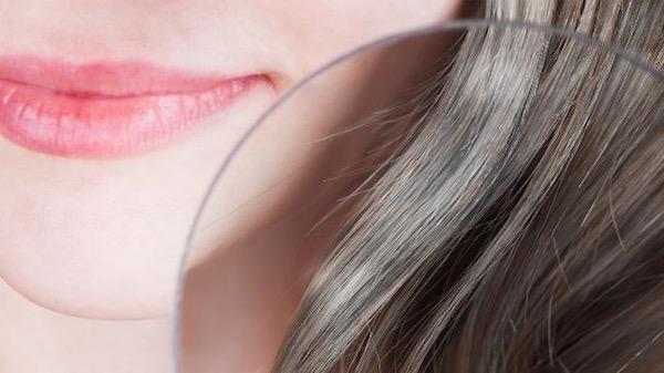 Nagyító alatt egy barna hajú hölgy első ősz hajszálai.