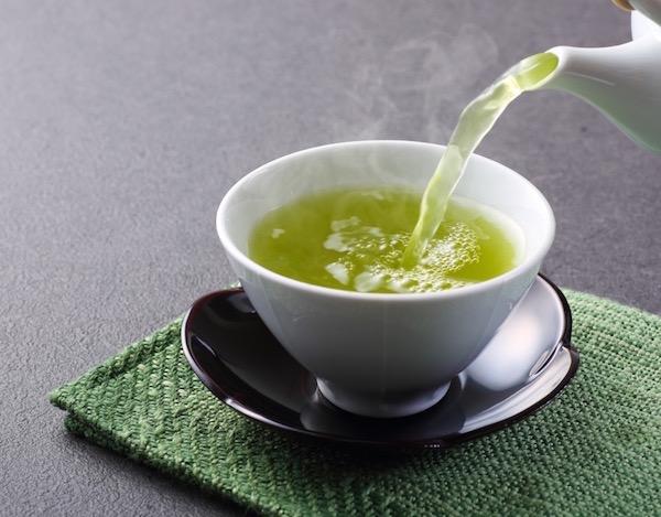 Forró zöld teát öntenek porcelán teáskannából egy csészébe.
