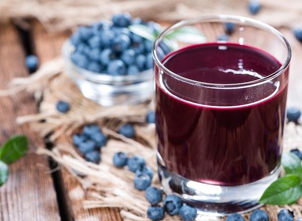 Friss áfonyából készített gyümölcslé, mellette a kék bogyók.