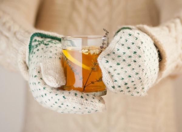 Gyógynövényes teát fog jó melegen felöltözve valaki, kezén vastag, mintás egyujjas kesztyű.