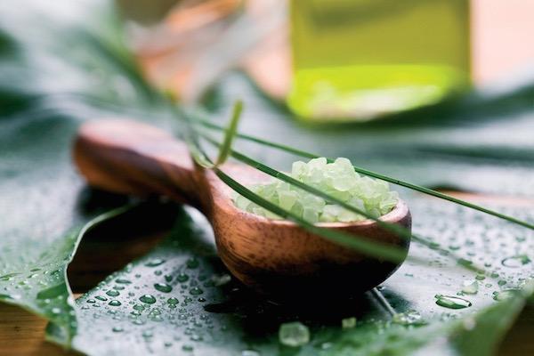 Vízcseppekkel pöttyözött leveleken zöld színű fürdősó bambuszból készült kanálkában, mellette citromfűolaj egy nagyobb üvegcsében.