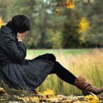 Fiatal nő egy őszi fa tövében tenyerébe temeti arcát.