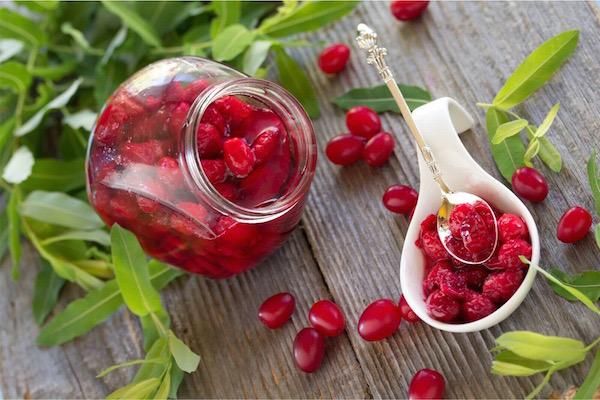 Somból készült lekvár egy csinos üvegcsében, mellette fehér kanálban a szirupos gyümölcs, az asztalon friss piros sombogyók.
