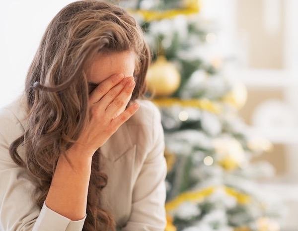 Karácsonyfa előtt ülő hölgy mély szomorúságban, arcát kezébe temeti.