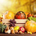 Őszi zöldségek és gyümölcsök egy nagy faládába téve: sütőtök, gomba, dió, alma, körte és szőlő.