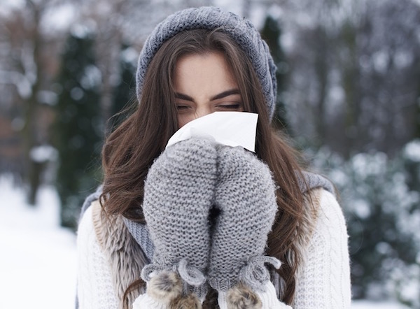Orrát fújja egy szürke kesztyűt, sálat és sapkát viselő fiatal lány kinn, a szabadban, egy havas vidéken.