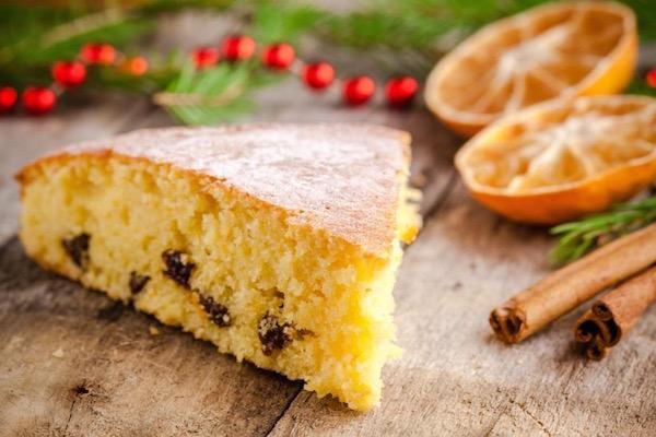 Fenyőág és piros dísz mellett mazsolás, mandarinos sütemény szeletkéje, mellette félbevágott mandarin és fahéjrudak.