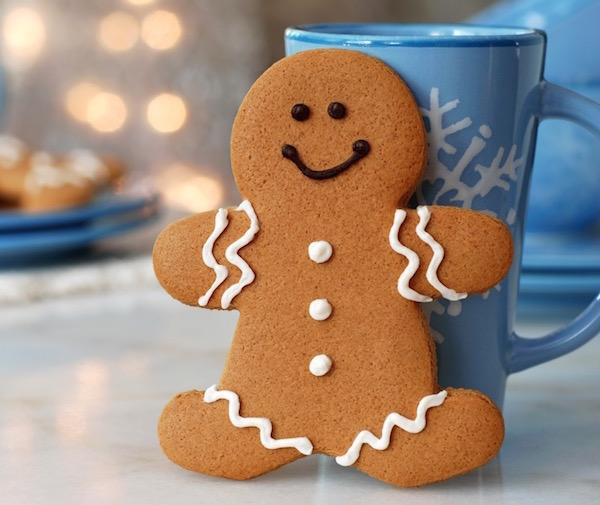 Mézeskalácsbábu egy kék színű, hópihével díszített bögréhez támasztva, a háttérben karácsonyi fények.