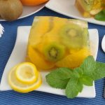 Kivis citromzselé egy kistányérra téve, mellette citromkarikák és citromfűlevélkék.