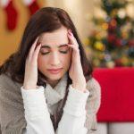 Fejfájásban szenved egy hosszú hajú hölgy a karácsonyfa előtt ülve, két kezét a homlokára szorítja.
