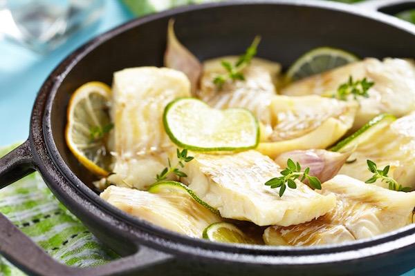 Serpenyőben lévő megsütött halszeletek citrom- és limekarikákkal, friss fűszernövényekkel.