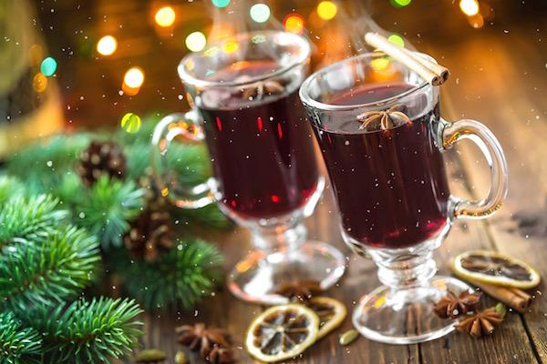 Karácsonyi hangulatú kép fenyőággal, tobozokkal, fényekkel és két pohár gőzölgő forralt borral.