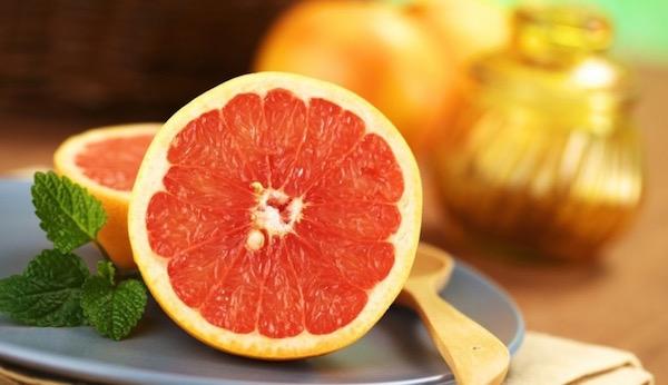 Félbevágott grépfrút egy szürke színű kistányéron.