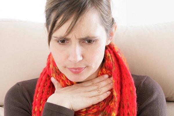 Sállal körbetekert fájó torkára helyezi kezét egy középkorú hölgy.