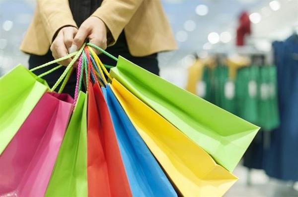 7 db színes papírtáskát fog kezében egy nő egy ruhaboltban.