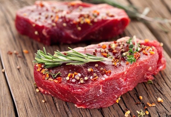 Két szép szelet vastagabb marhahús színes borssal megszórva, a tetejükön rozmaringággal.