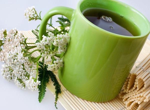 Zöld pohárban lévő cickafarkból készült tea nőgyógyászati panaszokra.