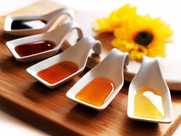 Többféle méz apró kis kínálókanalakba téve az asztalon, a háttérben két napraforgó virága.