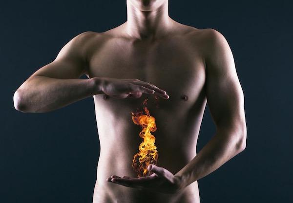 Férfi két keze közt mellkas alatt tüzet ábrázoló kép, mely a gyomorégésre utal.
