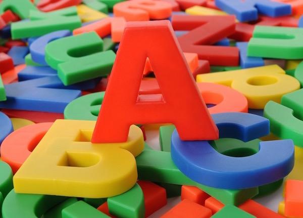 Színes műanyag játékbetűk tetején egy nagy piros A betű, mely egy kék B és egy sárga C betűn áll.