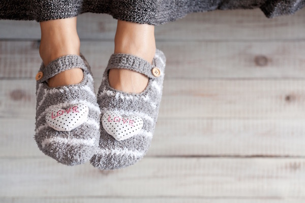 Csinos, kötött, szürke csíkos zoknicipő egy ágyról lelógatott lábon.