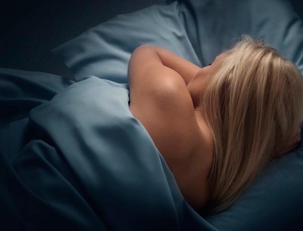 Hosszú, szőke hajú lány alszik éjjel egy acélkék ágyneműben.