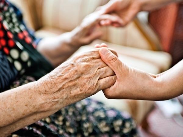 Idős néninek segítő kezet nyújt egy fiatal.