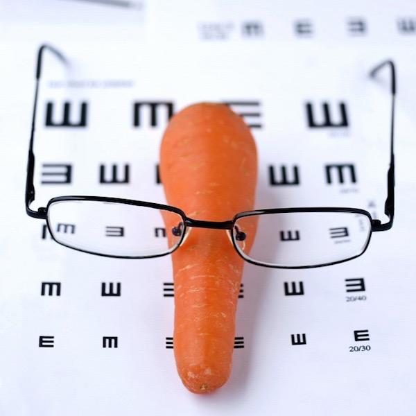 Látást ellenőrző kontrollvizsgálat papírlapjára téve egy sárgarépa, rajta egy szemüveg.