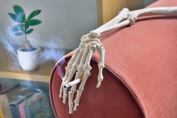 Csontváz kezében füstölgő cigaretta, amely a nappali kanapéján pihen.