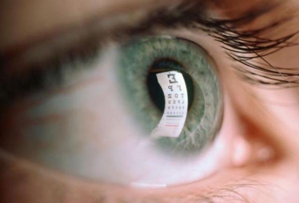 Zöldes emberi szemben visszatükröződik a látásvizsgálat olvasási táblája.