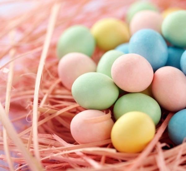 Gyógynövényekkel festett színes húsvéti tojások pasztellszínben pompázva egy fészekbe rakva.