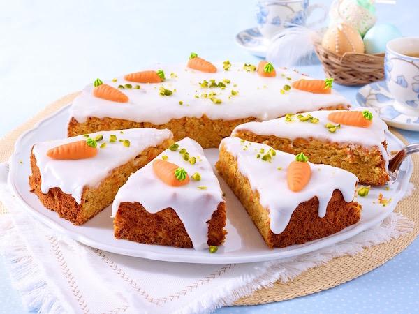 Dekoratív, húsvéti sárgarépatorta marcipán répákkal a tetején. A torta mellett az asztalon díszített tojások, teáspoharak.