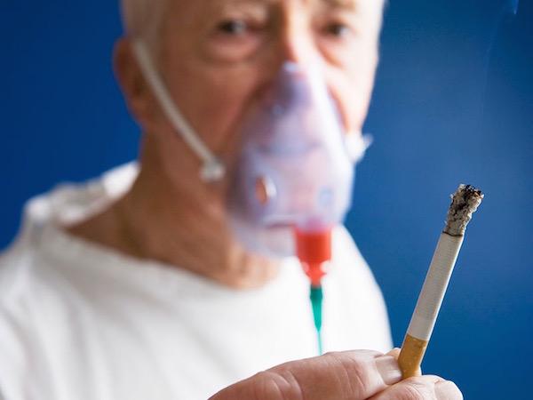 Idősebb férfi égő cigarettát tart a kezében, arcán oxigénmaszk.